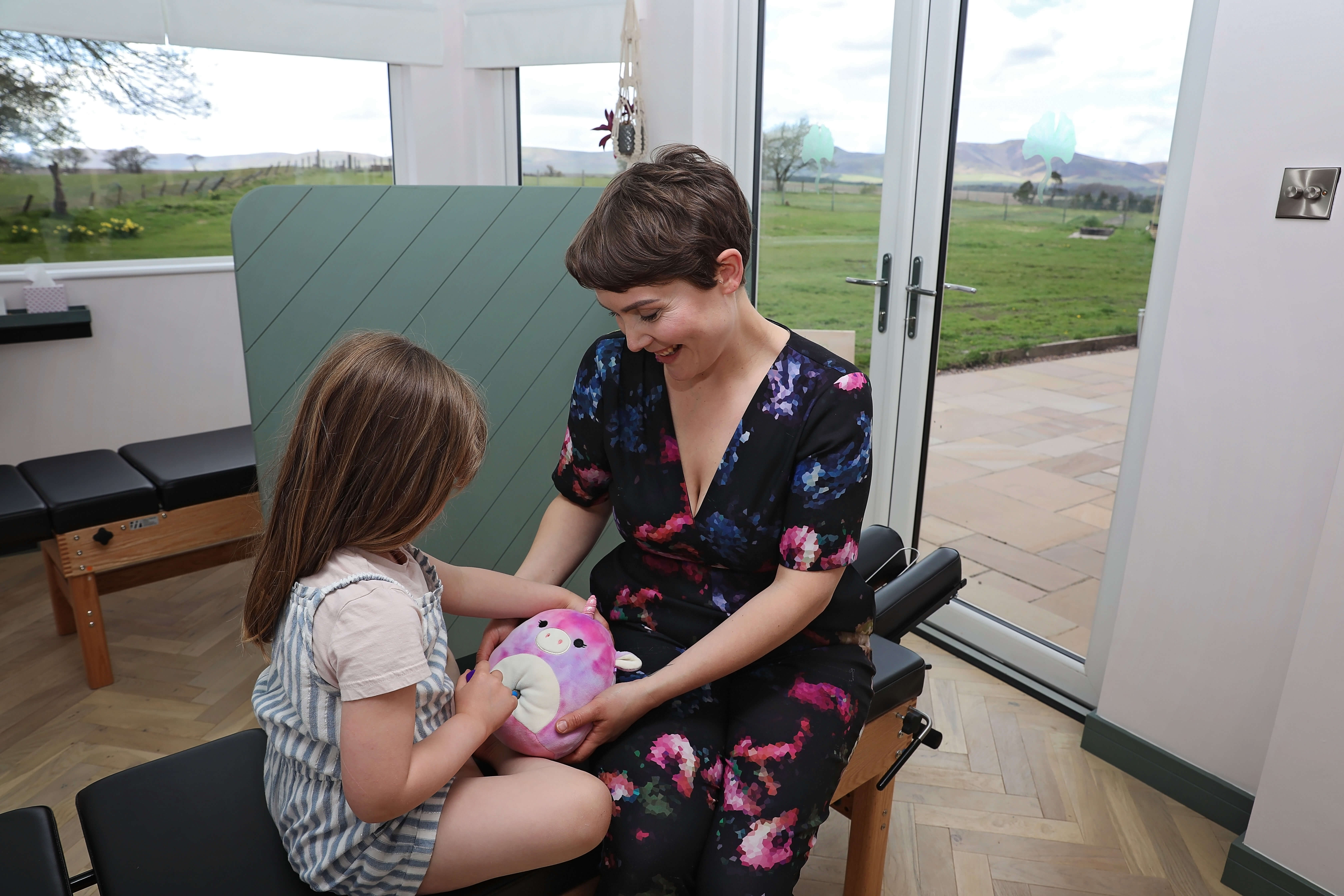 Chiropractor Naomi shows a young girl how to use an adjusting tool on her teddy